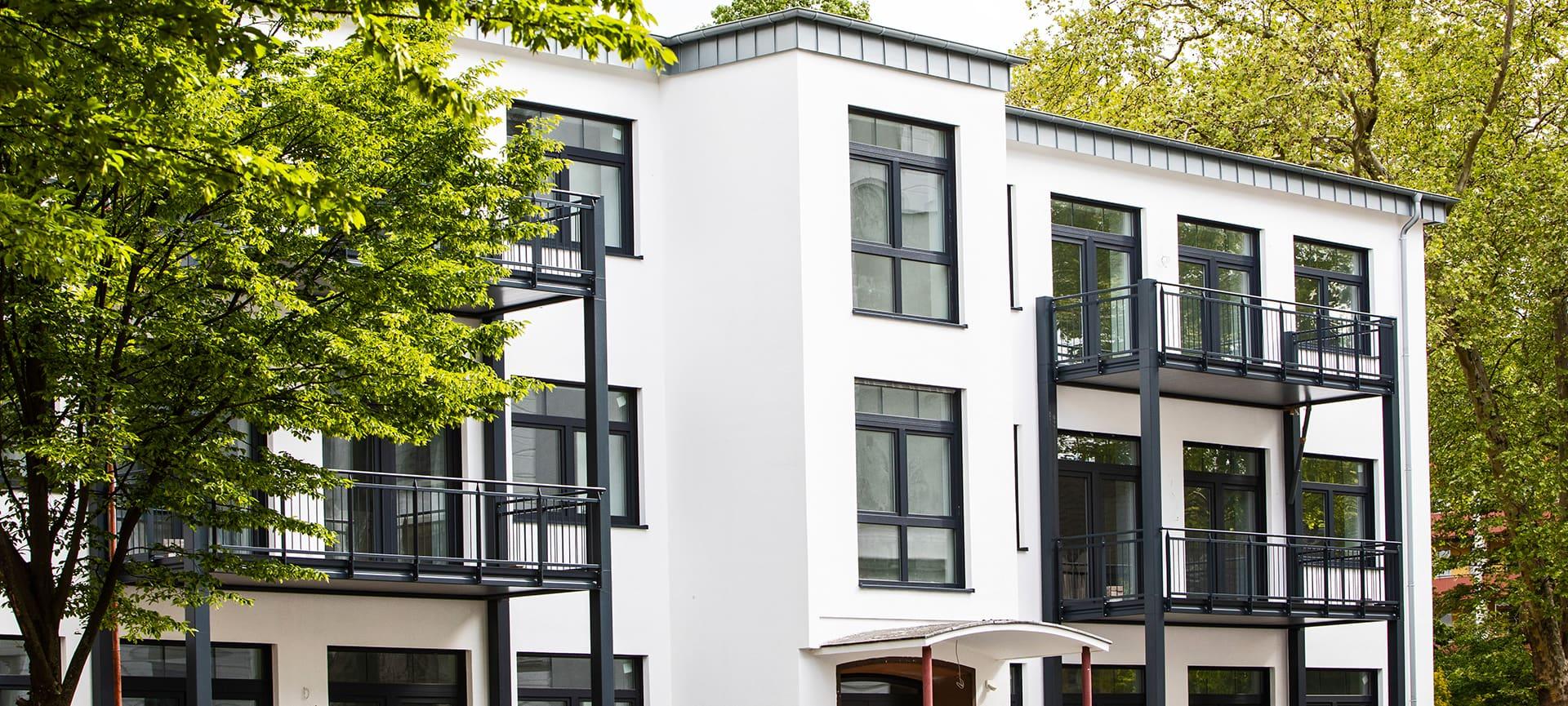 modernes weisses wohngebaeude mit schwarzen balkonen
